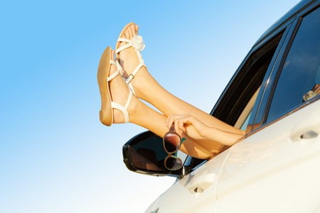 freedom concept: Summer road trip car vacation concept. Woman legs out the windows in car. Conceptual freedom, travel and holidays image with copy space.