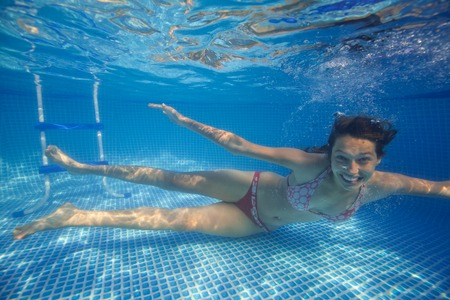 swim: Underwater woman smilling in swimming pool.