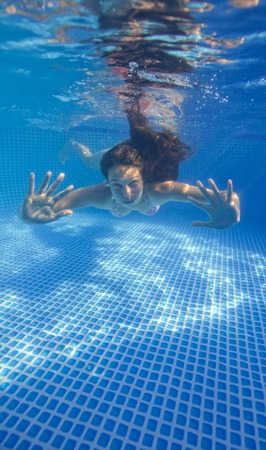underwater woman: Underwater woman smilling in swimming pool.