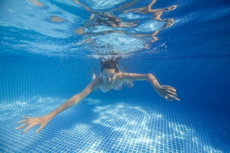 smilling: Underwater woman smilling in swimming pool.
