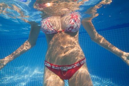 nude girl: Underwater woman body in bikiny posing in swimming pool. Stock Photo