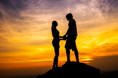 Silhouette of loving couple standing on a rock in sunset