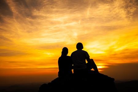 silhouettes lovers: Silueta de la pareja cari�osa que se sienta en una roca en la puesta del sol