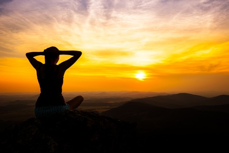 introspective: single adult woman silhouette on rock relaxing in sunset Stock Photo