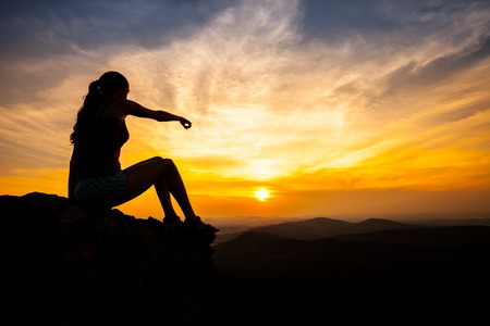 introspective: single adult woman silhouette on rock pointing on landscape