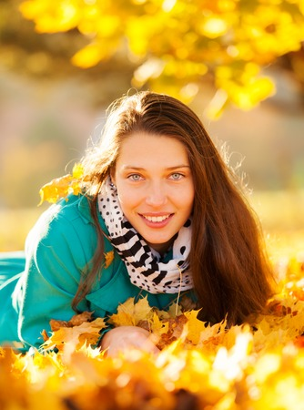 lying on leaves: Beautiful brunette girl lying in autumn leaves with smilling face. Concept of happiness and joy