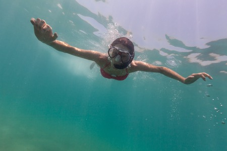 descends: Freediver woman descends into deep blue water Stock Photo