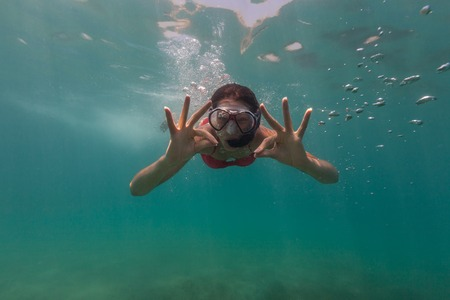 descends: Freediver woman descends into water, showing ok sign