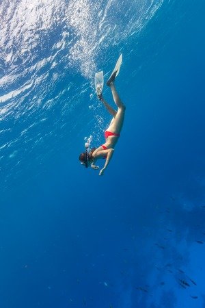 freediver: Freediver woman descends into deep blue water Stock Photo