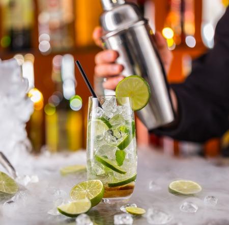 contadores: Mojito bebida cóctel en barra de bar con camarero de celebración agitador en el fondo