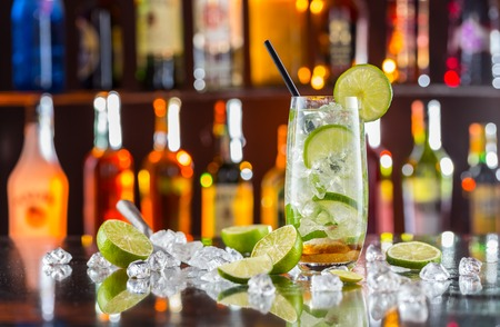 coctel de frutas: Mojito bebida cóctel en barra de bar con botellas de desenfoque en el fondo