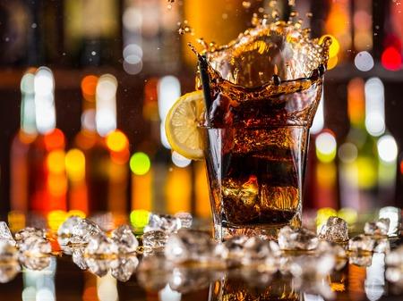 水しぶき、コーラのガラス カウンター バー上に配置