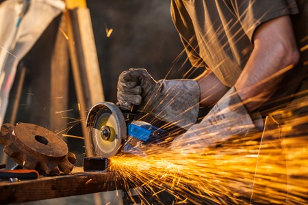 tool and die: Close-up of worker cutting metal with grinder. Sparks while grinding iron. Low depth of focus Stock Photo