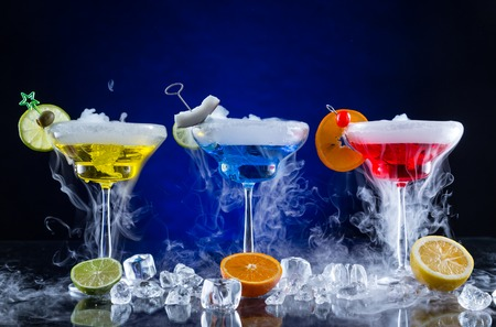 Martini drinks with dry ice smoke effect, served on bar counter with dark colored background Фото со стока