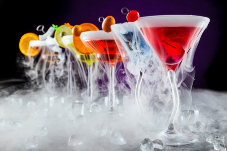 fruit bars: Martini drinks with dry ice smoke effect, served on bar counter with dark colored background Stock Photo