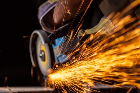 molinillo: Close-up of worker cutting metal with grinder. Sparks while grinding iron. Low depth of focus Foto de archivo