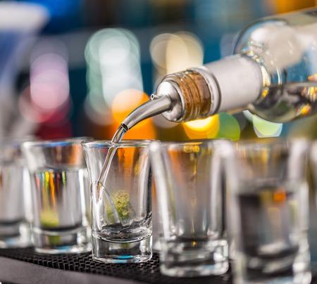 Barman schenkt hardgeest in glazen in detail