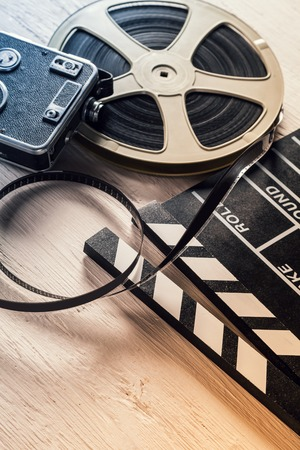 entertainment industry: Film camera, chalkboard and roll on wooden table