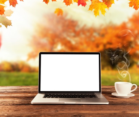 work table: Laptop placed on a wooden table with autumn landscape as background Stock Photo