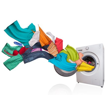 white wash: Colored laundry flying from washing machine, isolated on white background Stock Photo