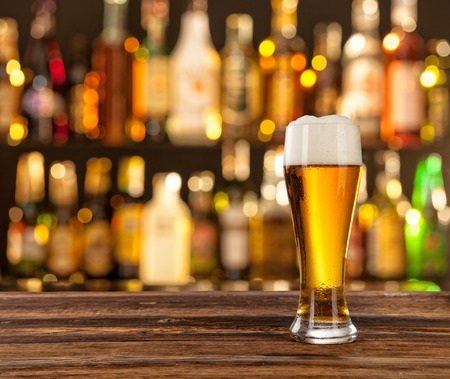 軽めのビールのグラスは、木製の机の上提供しています。バック グラウンドにバー