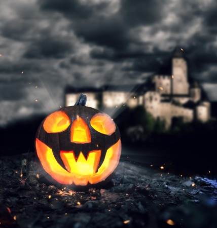 darkness: Halloween pumpkin on leaves at night. Castle on background Stock Photo