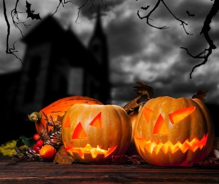 calabazas de halloween: Calabazas de Halloween en hojas en la noche. Iglesia Oscura en el fondo