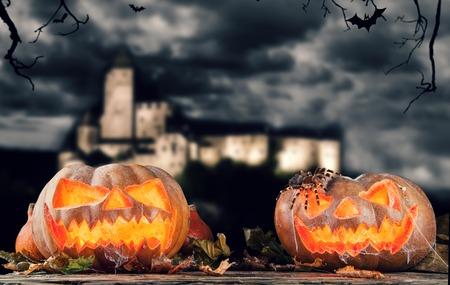 calabazas de halloween: Calabazas de Halloween en hojas en la noche. Castillo en el fondo Foto de archivo