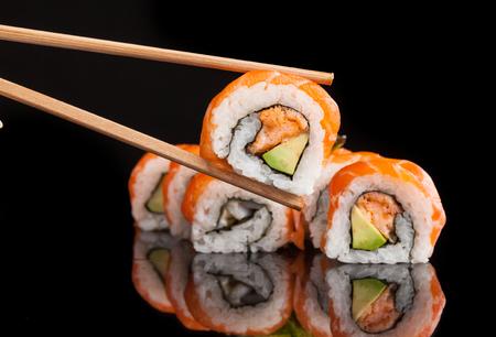 Maki sushi served on black background with reflection.
