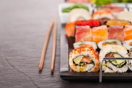 sushi: sushi pieces served on black stone with chopsticks Stock Photo