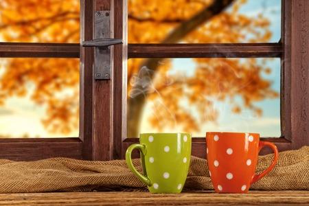 casa de campo: árboles otoñales ventana mirador de madera de época, un disparo desde el interior casa de campo con tazas de té Foto de archivo