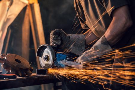労働者は、グラインダーで金属を切断のクローズ アップ。鉄を研削しながら火花します。低焦点深度