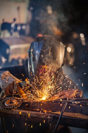 welding mask: Close-up of welder working in workshop. Low depth of focus