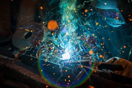 skilled labour: Close-up of welder working in workshop. Low depth of focus