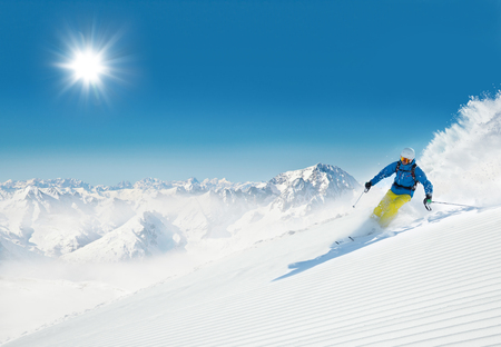 Man skier running downhill on sunny alpine slope