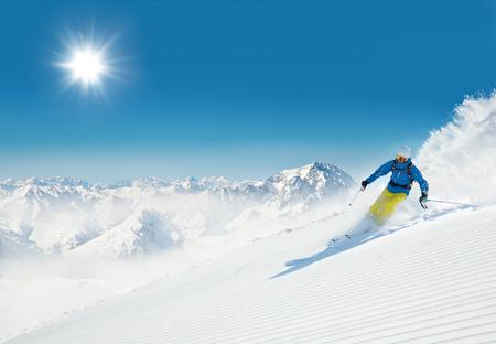 L'uomo sciatore in discesa sul pendio alpino pieno di sole