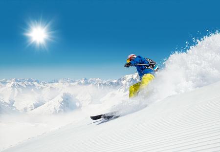 화창한 알파인 슬로프에서 내리막을 달리던 남자 스키어