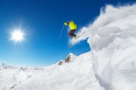 Jumping skier at jump with alpine high mountains