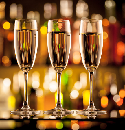 champagne glasses: Glasses of champagne in holiday setting, served on bar counter