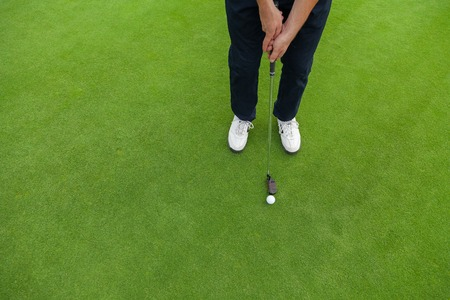 pies masculinos: Golf player at the putting green. Hitting ball into a hole Foto de archivo