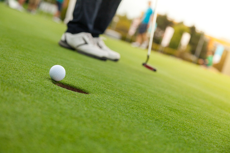 퍼팅 그린에서 골프 선수입니다. 구멍에 공을 친다. 스톡 콘텐츠