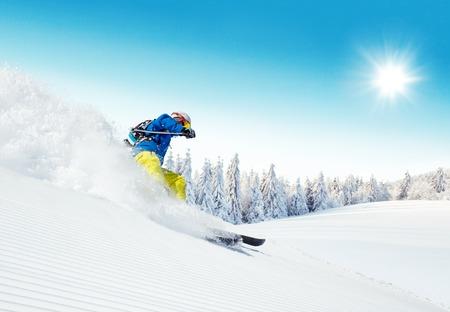 accion: Hombre esquiador corriendo cuesta abajo en laderas soleadas