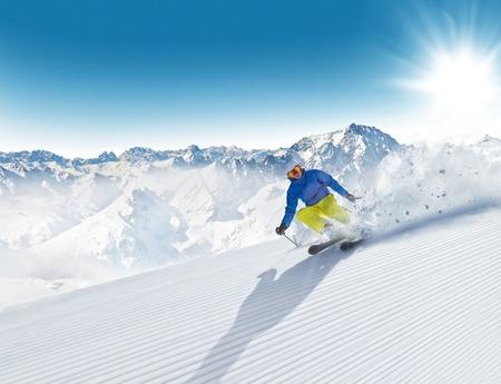 dangerous: Man skier running downhill on sunny Alps slope Stock Photo