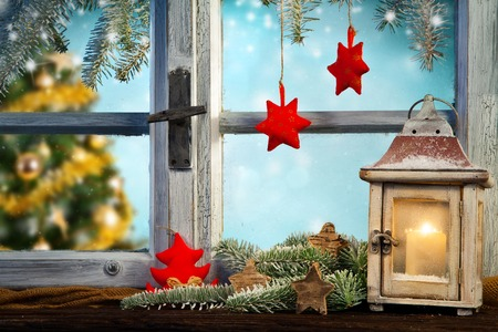 decoration: Lantern on window sill in winter mood. Christmas tree on background