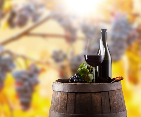 glass of red wine: Red wine bottle and glass on wooden keg. WIne grapes on background