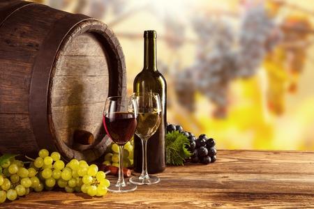 Botella de vino tinto y blanco y vidrio en barril de madera. Las uvas de vino en el fondo Foto de archivo - 46446668