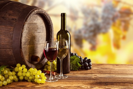Red and white wine bottle and glass on wooden keg. Grapes of wine on background Imagens