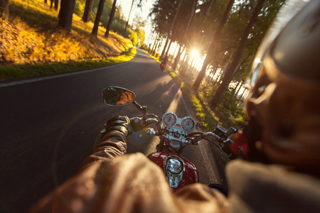 shot from behind: Biker riding motorcycle  on road in morning sunny day. Shot from behind Stock Photo