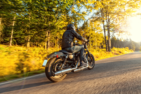 MOTORCYCLES: A young man riding a chopper on a road in morning sun