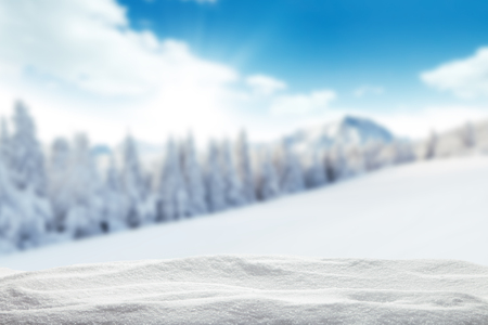 Winter background with pile of snow and blur landscape. Copyspace for text